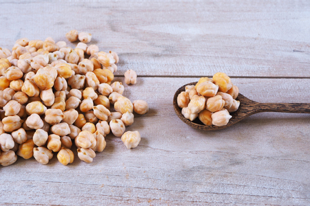 Close up of spoon of chickpeas on a wooden table.