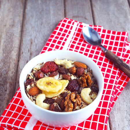 Close up of a healthy bowl of muesli with dried fruit and nuts on a wooden background.