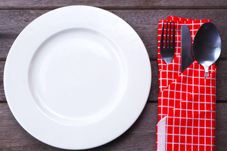 Top view of empty dish with knife, fork and spoon on old wooden background. Banco de Imagens