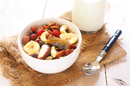 Close up of a healthy bowl of muesli mixed with dried fruit and nuts and almond milk on a wooden background.