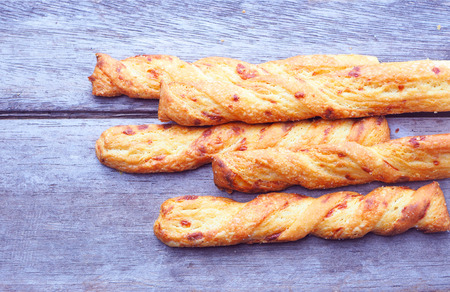 Top view of crispy cheese bread sticks on a wooden background.
