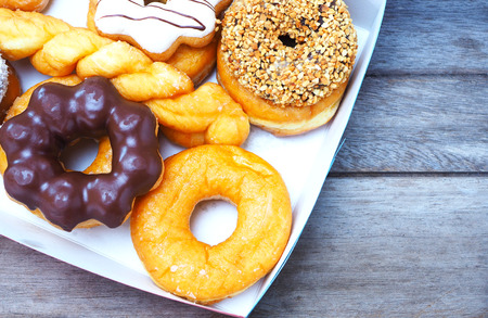 Top view of a box of donut on a wooden table. Banco de Imagens
