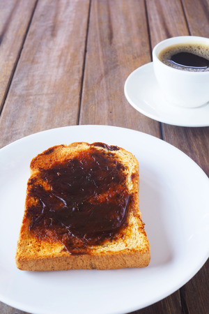 Close up of Australian breakfast with savory spread on a sliced wholewheat toast and black coffee on a wooden table. Banco de Imagens