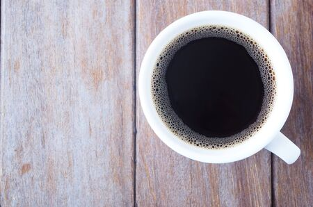 Top view of a cup of black coffee on a wooden table.