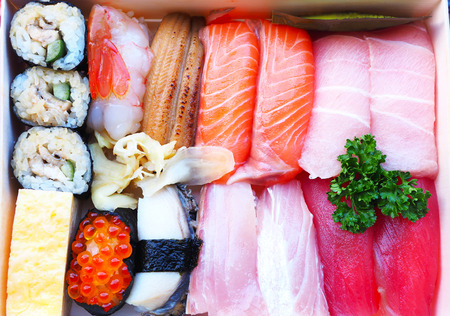 Top view of traditional Japanese sushi box with rice rolls, raw fresh salmon, prawn, tuna, abalone and sweet egg.