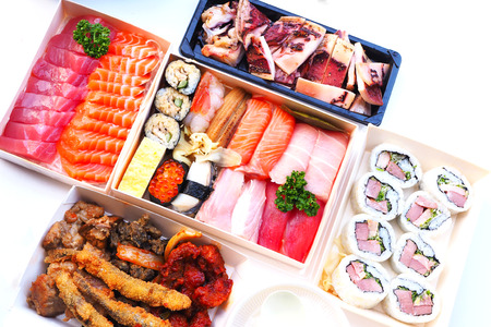 Topview of Japanese lunch boxes with sushi, grilled squid, fried fish and sashimi set on a white table.