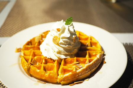 A breakfast of honey waffle with almond and whipped cream. Banco de Imagens