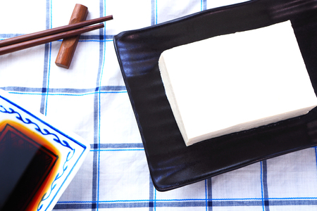 Top view of soft bean curd on a black plate.