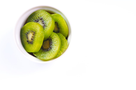 Top view of sliced kiwi fruit in a white bowl on white background.