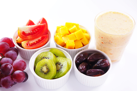 Close up of healthy glass of mixed fruits smoothie with fruits on a white background.
