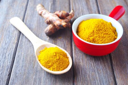 Close up of turmeric powder in a wooden spoon, bowl and fresh turmeric roots on a wooden table.