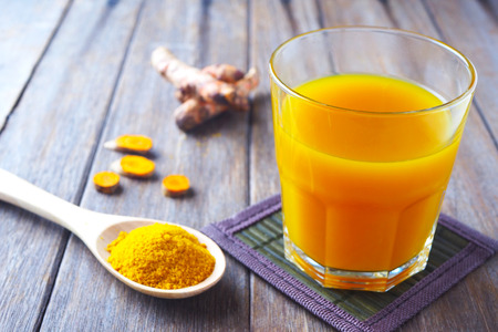 Close up of immunity boosting spicy turmeric juice and powder on a wooden table.