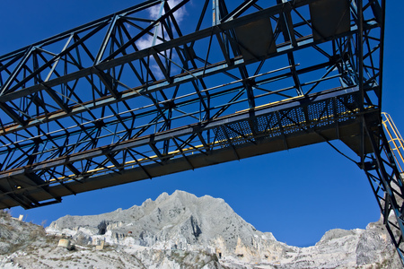 In a marble deposit on the Carrara mountains, an overhead crane is used to move the white marble blocks.