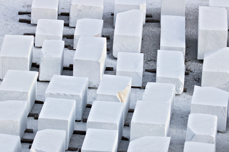 The blocks of white Carrara marble, after being extracted from the quarry, are deposited in outdoor squares, not far from the extraction sites. Banque d'images - 122617736