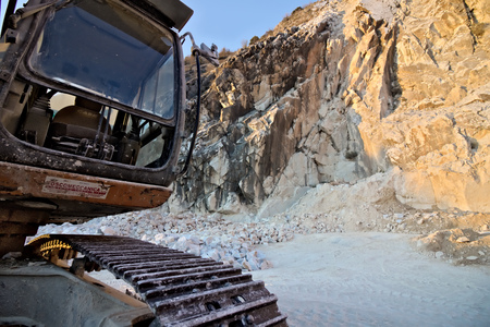 In the mountains of the Apuan Alps, above the city of Carrara, white marble has been mined since Roman times. The mechanical means and the excavators help the man in the extraction. 스톡 콘텐츠 - 122617744