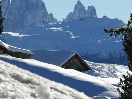 Snow covered mountain house. In the background the mountains of the Dolomites.