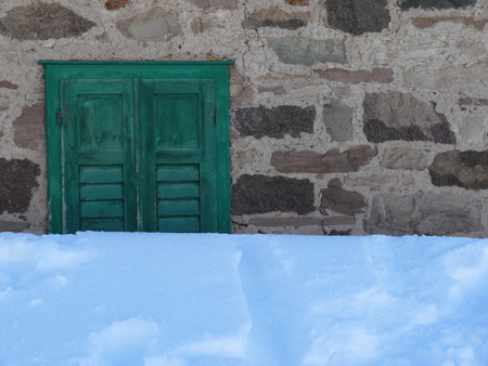 The snow cloak almost completely submerges a facade of a building.