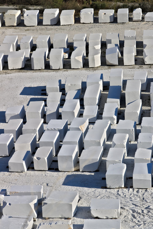 The blocks of white Carrara marble, after being extracted from the quarry, are deposited in outdoor squares, not far from the extraction sites. Banque d'images - 122618408