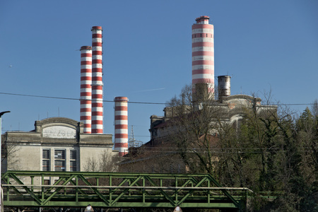 The industrial buildings and chimneys of the thermoelectric power plant located near the Naviglio Grande canal 40 km from Milan. Standard-Bild - 122618571