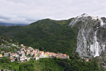 Colonnata, Carrara, Tuscany, Italy. View of the village of Colonnata, where the famous lard is produced. On the right a cascade of marble debris. Northern Tuscany near Carrara.