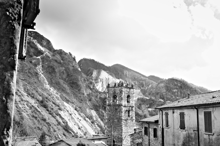 Colonnata, Carrara, Tuscany, Italy. Bell tower of the church built with white marble pebbles. The ancient village, famous for its lard, is located in the heart of the Carrara marble quarries.