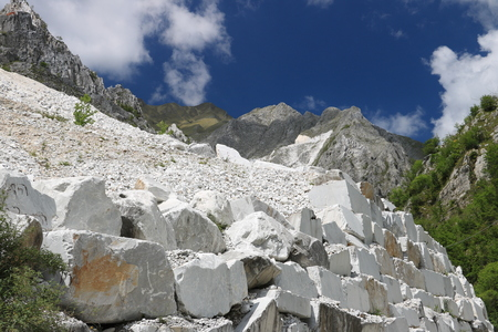 White Carrara marble quarries near Colonnata. A steep street with white marble blocks and the mountains of the Apuan Alps. Stockfoto