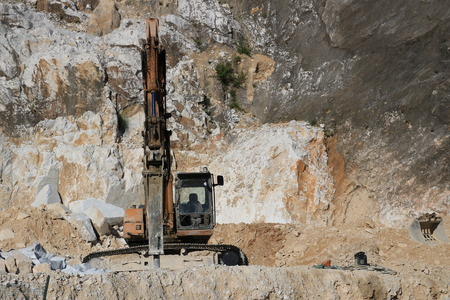 Carrara, Italy. Excavator with demolition hammer in a Carrara marble quarry. A large excavator shovel in a quarry in the Apuan Alps mountains.