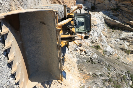 Carrara, Tuscany, Italy. Bulldozer in a Carrara marble quarry. A large  mechanical shovel in a quarry in the Apuan Alps mountains. Reklamní fotografie
