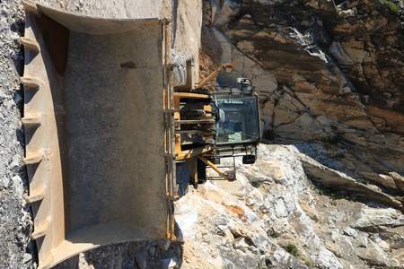 Carrara, Tuscany, Italy. 05312019. Bulldozer in a Carrara marble quarry. A large mechanical shovel in a quarry in the Apuan Alps mountains.