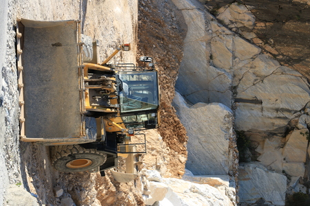 Carrara, Tuscany, Italy.  Bulldozer in a Carrara marble quarry. A large mechanical shovel in a quarry in the Apuan Alps mountains.