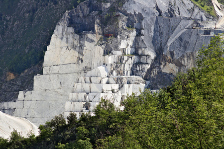 White Carrara marble quarry in the Apuan Alps. A mountain peak near Colonnata with blue sky and clouds. Stockfoto
