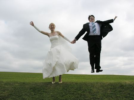 bride and groom jump on meadow Stock Photo - 423114