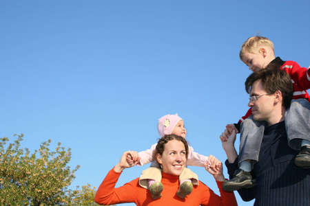 family with children on shoulders photo