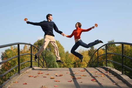 full strenght: jump couple on autumn bridge