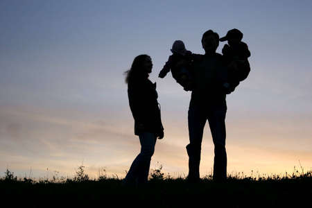 family with children on hands, sunset sky photo
