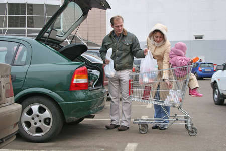 shopping carriage: family put shop bags in car