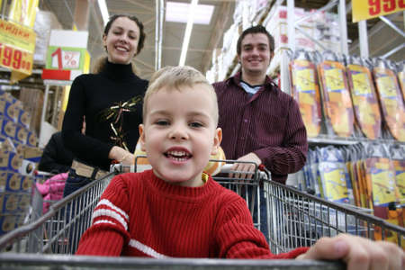 shopping carriage: boy with parents in shop