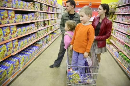 tiendas de comida: familia de cuatro personas en tienda  Foto de archivo