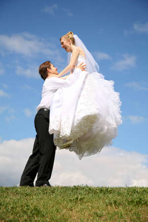 fiance raises bride on the hands on to the meadow Stock Photo - 2281703