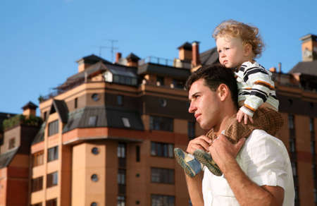 child on the shoulders of the father photo