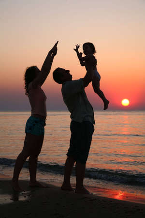 ashore: Mummy with daughter and grandfather on sunset ashore Stock Photo