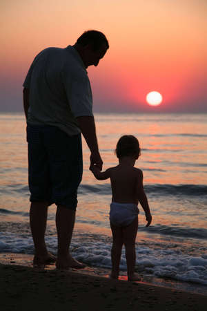 back lit: Grandfather with granddaughter on sunset at sea Stock Photo
