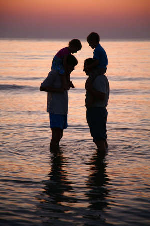 Two men in sea with children on shoulders on sunset photo