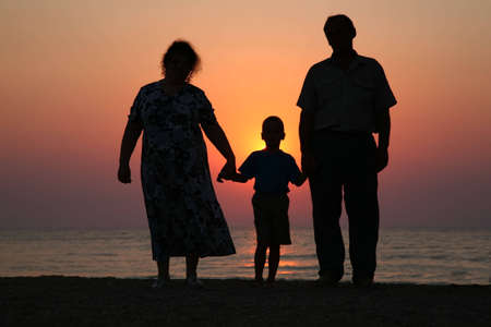 Grandfather with grandmother and the grandson against the background of sunset photo