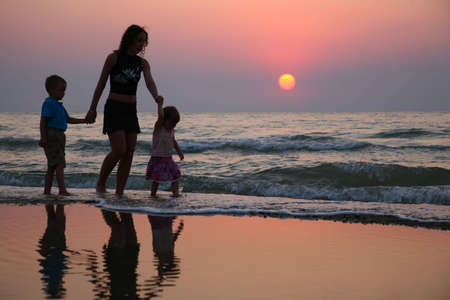 mom and child: Mother with children ashore on sunset Stock Photo