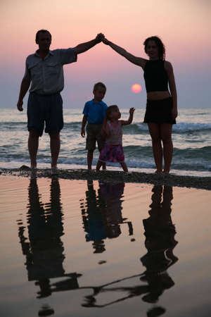 ashore: Mother with children and grandfather ashore on sunset