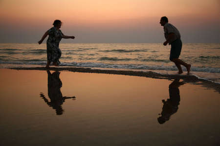 senile: Grandfather with grandmother on sunset at sea running Stock Photo