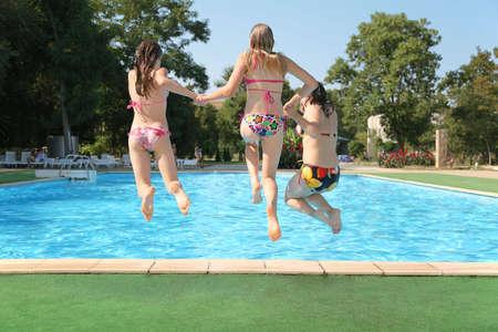 meisje zwemmen: Drie meisjes springen in zwembad