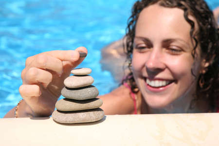 happynes: The woman builds a figure of stones about water Stock Photo