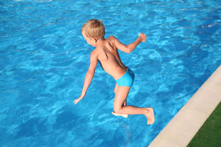 skin diving: The boy jumps in pool.
